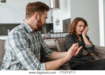 Photo of angry young quarrel loving couple sitting on sofa indoors. Looking aside. Focus on man.