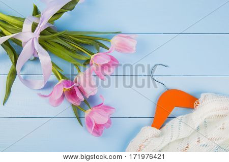 Bouquet Of Tender Pink Tulips And Hanger With Clothes On Blue Wooden Background