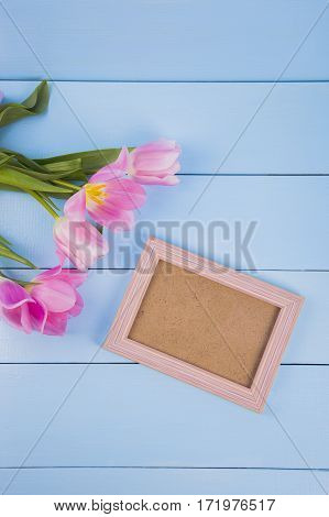 Bouquet Of Tender Pink Tulips With Empty Photo Frame On Blue Wooden Background
