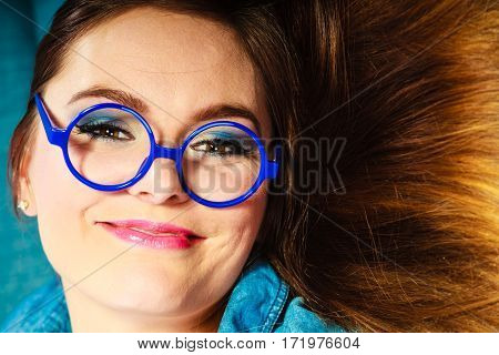 Eyewear. Young attractive woman face in blue glasses closeup
