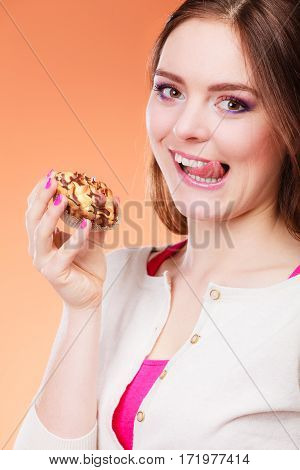 Bakery sweet food and people concept. Woman enjoying cake cupcake licking lips orange background