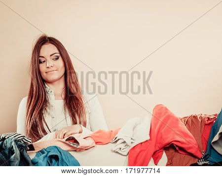 Content Woman Sit Behind Sofa Full Of Clothes.