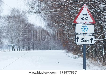Snow covered road, winter driving with road sign - slippery road.