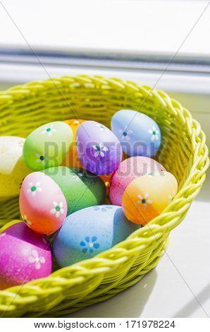 Mix Of Colorful Easter Eggs In Wicker Basket Near Window
