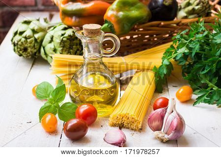 Clean eating concept healthy mediterranean diet ingredients for Italian meal spaghetti tomatoes basil olive oil garlic peppers artichokes on wood kitchen table outdoors
