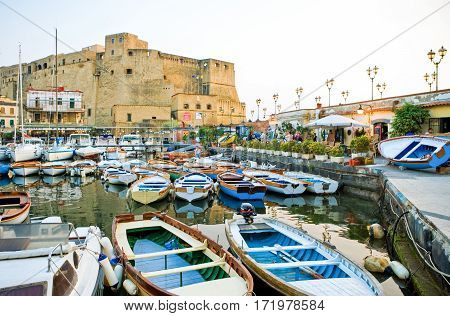 Naples Italy - April 21 2006: Sunset view of the Castel Dell'Ovo fortress with the marina in the foreground
