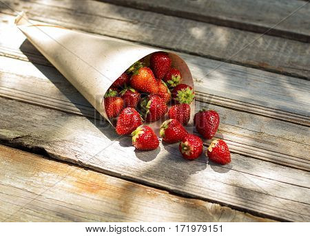 Strawberries In A Paper Bag On An Old Wooden Background