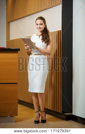 Woman standing with tablet and looking in frame. Female dressed in white medium length sheath dress. Neck and waist decorated with gold accessories.