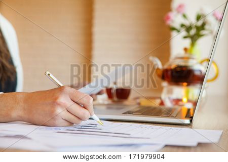 Female hands writing pen in white case on paper. Open laptop, teapot with tea fueled by candle, little cup honey, full cup tea and yellow vase with flower illuminates daylight window.