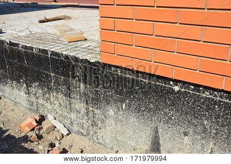 Waterproofing a new brick house foundation with spray on tar. Construction techniques for waterproofing basements and foundations.
