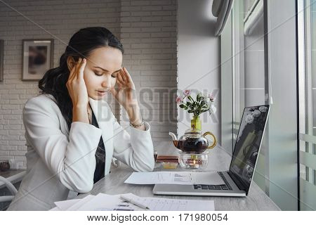 Awful headache makes woman suffer during working day. Girl tired of work at laptop. Sad depressed lady working at table at daytime. Paper with deadline project around her. Overworked person