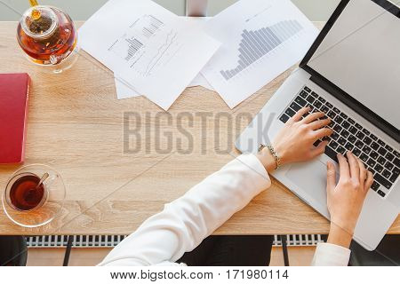Female hands typing on laptop keyboard. Paper with charts, teapot filled with tea, glass saucer and cup with drink, table-book and laptop lying on desk.