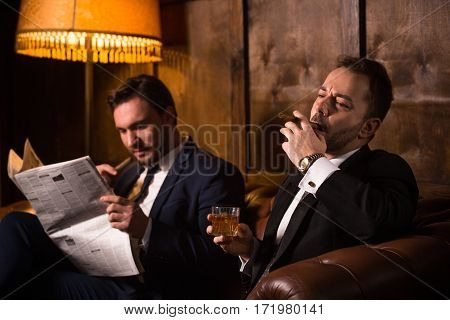Rich businessmen resting and relaxing in men's club. Happy men drinking whiskey and smoking cigars. One man reading newspaper.
