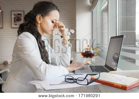 Elegant lady holding nose with closed eyes because of stress and migraine at work. Person tired of work sitting at table with laptop, papers, tea, glasses and folders. Exhausted woman at workplace
