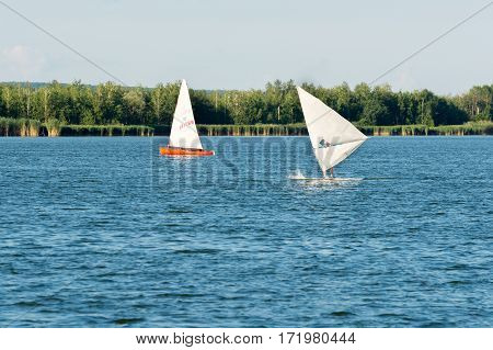 KURCHATOW, RUSSIA - JUNE 23, 2016: Windsurfers are trained on a large lake. Evening shot.