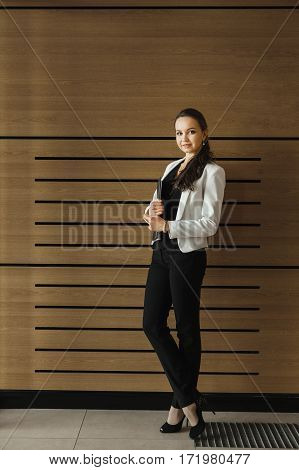Pretty woman in business suit holding black folder with documents. Female on high heels with crossed legs. European woman full length in white jacket. Perfect skin and sensitive look