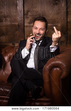 Much money is ability to send all in ass. Handsome rich man smoking cigar and giving fuck off while sitting on sofa in men's club.