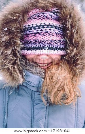 Portrait of girl with covered face with her hat outdoors in the wintertime