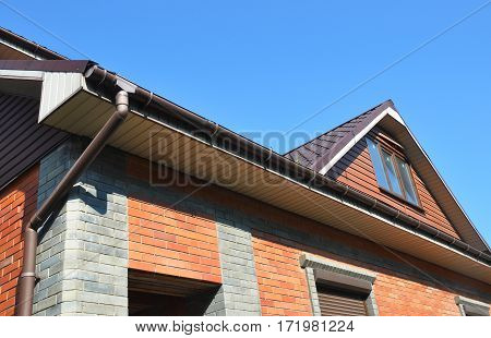 Attic with rain gutter pipe. Rain gutter downspout pipeline.