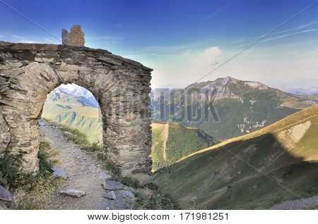 old stone arch in a hiking footpath on beautiful mountain landscape