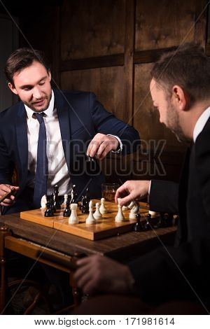 Handsome rich businessmen playing chess showing rivalry or competition between their business of companies, enterprises, firms. Business competition concept.