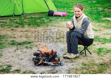Smiling woman dressed in trekking clothes warm up near the campfire holding a hot cup of tea. Active outdoor recreation, holiday camping.
