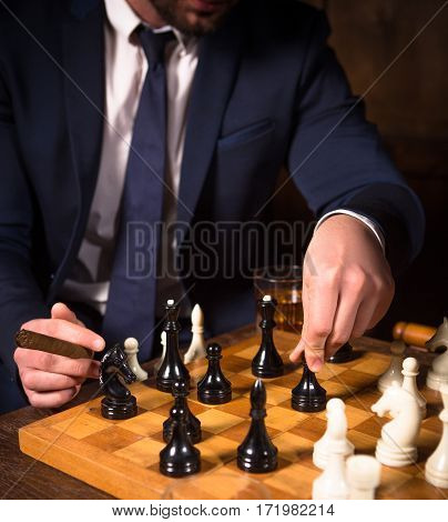 Business concept. Competition and rivalry concepts. Closeup of chessboard with white and black chess pieces on. Man ready to play with partner.