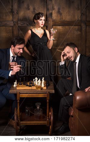 Handsome executive rich men playing chess in restaurant. Men spending free time in restaurant and thinking about business.
