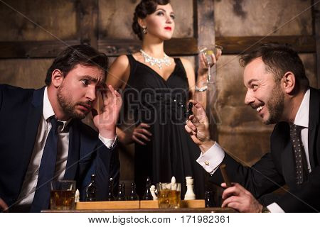 Two rich men playing chess in restaurant like rivalry or competition between their businesses. Elegant lady posing on background. Business concept. Luxury concept.