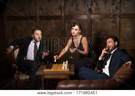 Intelligent woman concept. Beautiful lady putting cocktails on table and looking surprised at her man's partner or competitor. Business concept.