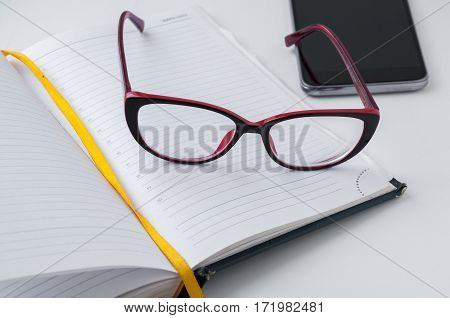 Red Glasses Lying On The Open Notepad Next To Your Smartphone
