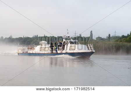 Kurchatov, Russia - JUNE 23, 2016: Reporters sail on a pleasure boat on the reservoir of Kursk NPP. Foggy morning.