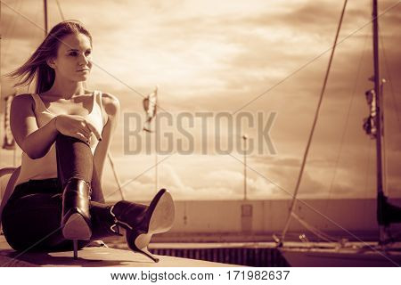 Resting and relaxation. Young beauty woman relaxing on marina on fresh air. Fashionable blondie girl spending time outdoor.