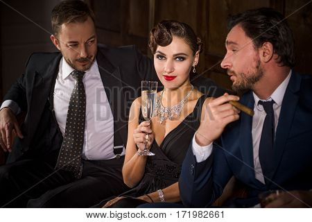 Rivalry or competition between two handsome rich executive men for elegant lady with red lips. Pretty lady sitting with glass of champagne. Richness, wealth, luxury concepts.