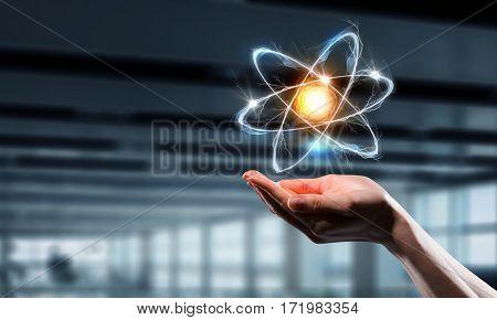 Atom icon in palm . Mixed media . Mixed media