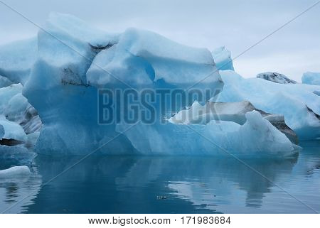 a blue splinter of ice from Vatnajokull glacier swimming on a reservoir on Iceland