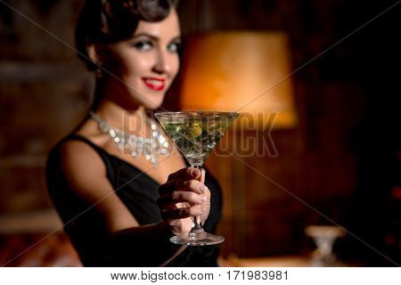 Wealth concept. Rich vamp lady with red lips giving glass of alcohol cocktail to camera. Happy lady smiling for camera in restaurant atmosphere.