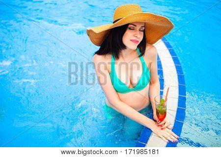 Beautiful Brunette Woman In Bikini And Hat, Enjoying Mojito Cocktail In A Swimming Pool, Summer Time