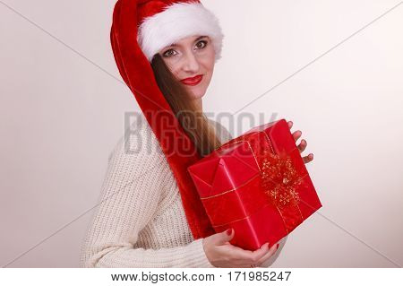 Curious woman with gift. Young girl holding ribbon box wearign santa cap. Christmas celebration holiday relax concept.