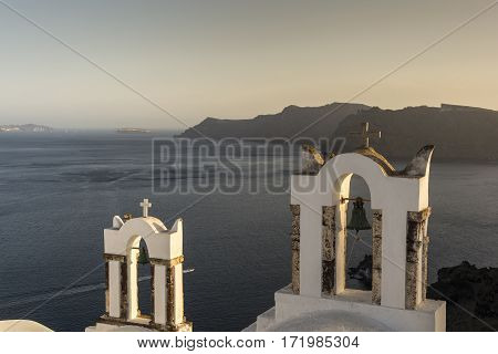 Traditional church belfry at sunset in Oia Santorini Greece