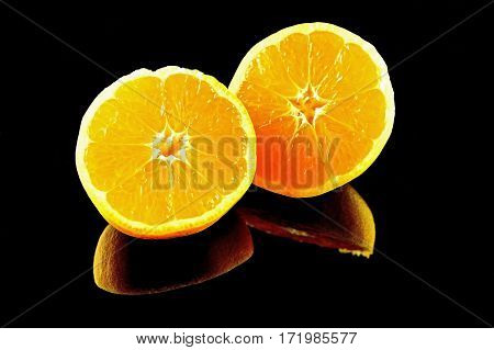 Two halfs of mandarin fruit on black background. Fresh and heath tropical citrus fruit.