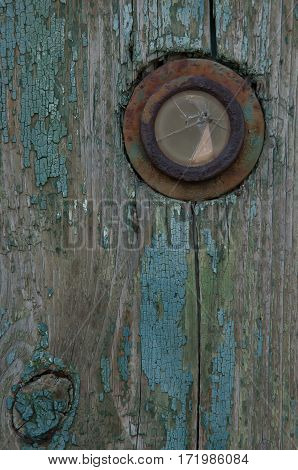 Frustrated peephole on the old wooden door