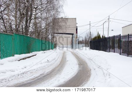 Winter Street With Metal And Gree Wooden Fences Between Road