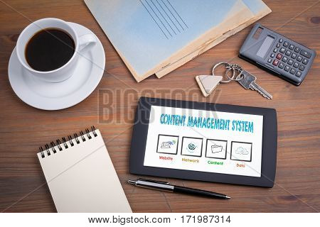 Content Management System, business concept. Text on tablet device on a wooden table.