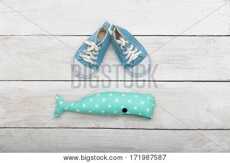 blue sneakers for a small child and a toy on a wooden background. View from above