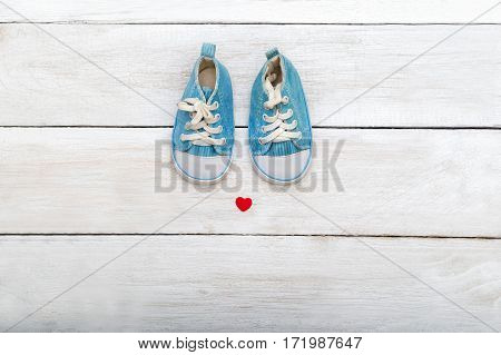 Baby shoes on wooden background. flat lay