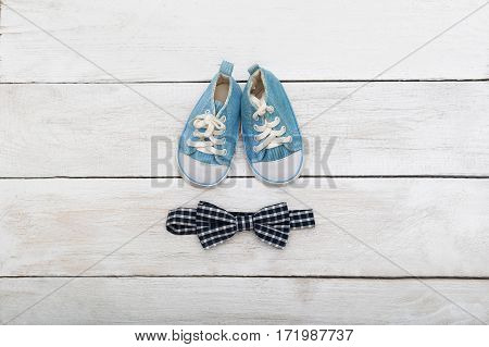 blue sneakers for a little boy and a bow tie on a wooden background. flat lay