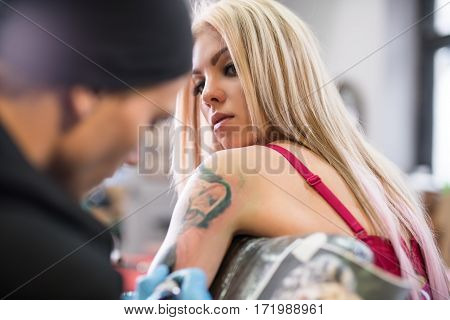 Young sexy blonde in pink top in tatto studio shot with tattoo master drawing tattoo on girl s forearm