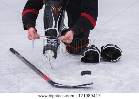 hockey player before the game tying laces on skates