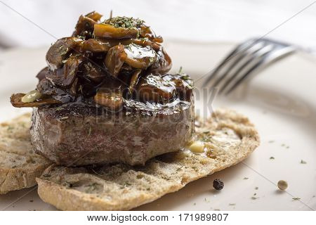 Beef Steak Fillet Covered with Mushroom Sauce on Toasted Baguette Bread with Melting Butter and Herbs